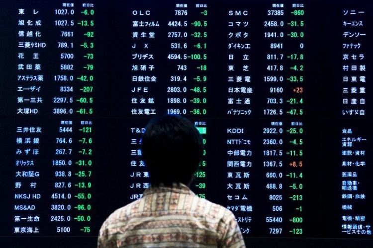Женщина изучает котировки на табло Токийской фондовой биржи 29 июня 2015 года. Азиатские фондовые рынки снизились в понедельник в страхе перед дефолтом Греции. REUTERS/Thomas Peter