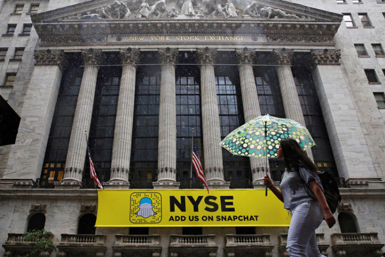 A woman passes by the New York Stock Exchange (NYSE) during the morning commute in New York City, U.S., October 21, 2016.  REUTERS/Brendan McDermid